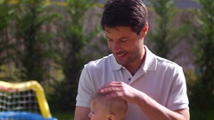 Young father holding his baby toddler in his arms Candid scene Stock Footage