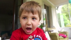 Handsome 5 year old boy portrait Opening mouth widely in a funny Stock Footage