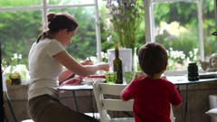 Candid shot of boy with his mom in outdoor balcony during supper time Stock Footage