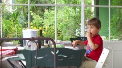 Child eating lunch by himself in outdoor balcony and with green patio Stock Footage