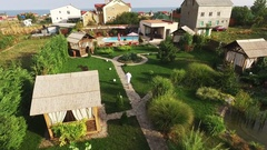 Caucasian male in white bathrobe slowly walking in garden with pool. Footage Stock Footage