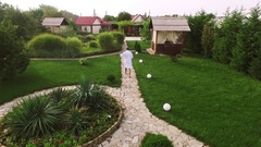 Caucasian male in white bathrobe slowly walking in private garden. Footage from Stock Footage