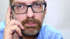 Bearded Man With Glasess Talking At His Mobile Phone Stock Footage