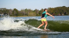 A young woman wake surfing behind a boat on a lake, slow motion. Stock Footage