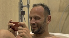 Happy man playing game on smartphone sitting n bathtub at home Stock Footage