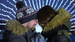 Happy romantic couple embracing at Christmas city street. Slow motion Stock Footage