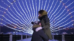 Man spinning around his girlfriend in his hands. Winter christmas evening Stock Footage
