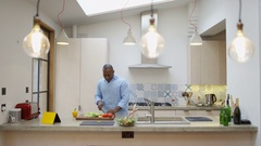 4K Happy guy listening to music on tablet & dancing while he prepares a meal Stock Footage