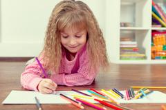 Little beautiful girl draws pencil on the floor in the children's room Stock Photos