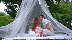 Romantic couple kissing in decorations for wedding photo session at park Stock Footage