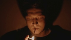 Man ignites and smokes a cigarette in darkness close-up Stock Footage
