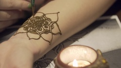 The master draws mehendi on the girl's hand. Beautiful patterns from henna Stock Footage