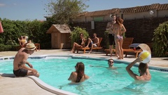 Group of friends playing in pool with beachball talking smiling lying on lounge Stock Footage