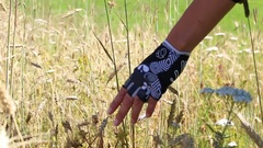 Mountainbiker hand with gloves straving through a corn and flower field wit.. Stock Footage