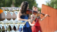 Violinists playing on the background wine glasses with champagne Stock Footage