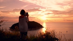 Young woman taking pictures of sunset over ocean using tablet computer Stock Footage