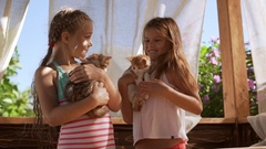 Two young girls holding ginger cute kittens on hands in slowmotion Stock Footage