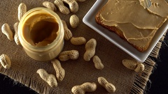 Tasty peanut butter being spread on white toast Stock Footage