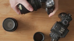 Man changing lenses of an analogue photo camera Stock Footage