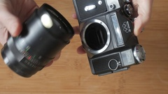 User mounts a telephoto lens on an old classic photo film camera Stock Footage