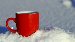 Cup of hot coffee or tea stands on the snow Stock Footage