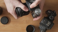 User mounts a macro extension lens on a film camera Stock Footage