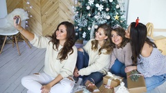 Smiling girlfriends taking a selfie with smarphone. Christmas mood Stock Footage