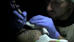 Tattooer At Work In Dark Tattoo Salon Stock Footage