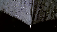 Raindrops falling on black umbrella in slow motion Stock Footage