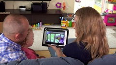 Parents with little daughter girl watch family movie video on tablet computer Stock Footage