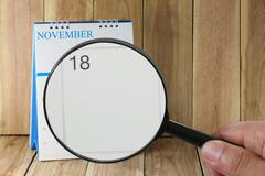 Magnifying glass in hand on calendar you can look Eighteen days of month,Fo.. Stock Photos