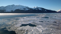 River Ice and Distant Mist Mountains Lateral Scenic Aerial HD Stock Footage