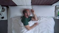 Lazy man continues sleeping in the morning when ring the alarm Stock Footage