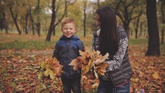 Cheerful red-haired little boy with his mother compre throw up yellow leaves in Stock Footage