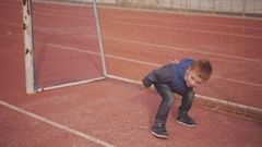 Cheerful red-haired little boy playing with a ball near a football goal at the Stock Footage