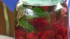 Macro Red Cherry Berries Compote in a Glass Jar Stock Footage