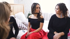 Four beautiful women have gossip talks and discuss problems while sitting on bed Stock Footage
