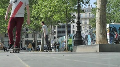 A young man does a trick while riding his skateboard in a town square, slow moti Stock Footage
