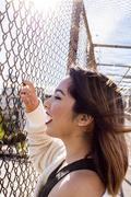 Smiling Asian woman holding chain-link fence on footbridge Stock Photos