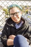 Smiling androgynous Asian woman leaning on chain-link fence Stock Photos