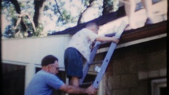 Dad & grandpa help the kids down from the roof, 3945 vintage film home movie Stock Footage
