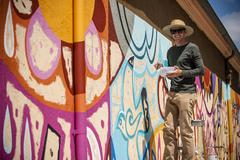 Portrait of man standing on ladder painting mural on wall Stock Photos