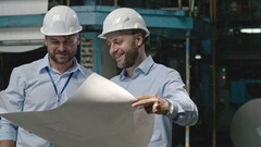 Cheerful Engineers with Blueprint at Factory Stock Footage