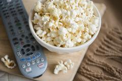 Bowl of popcorn and remote control Stock Photos
