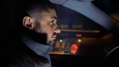 Man behind the wheel of a car driving on the evening streets Stock Footage
