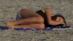 Young woman sleeping on the beach Stock Footage