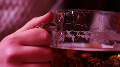Woman drinks a large glass of beer with foam in a pub Stock Footage