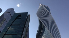 Unusual twisted skyscraper beside other tall buildings, camera tilt down Stock Footage