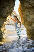 Caucasian woman stretching leg leaning on rock formation at beach Stock Photos