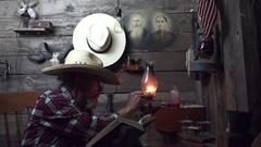 Cowboy Western reading by kerosene lantern Stock Footage